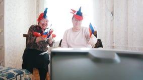 两名在俄国辅助部件和愉快地挥动的俄国旗子的年长妇女看着电视 影视素材