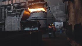 两名在黑暗的肮脏的工厂背景的工作者在制服和盔甲看法从后面的  英尺长度 两位雇员显示器 股票视频