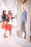 两名在购物中心的美好的妇女窗口购物 免版税库存图片