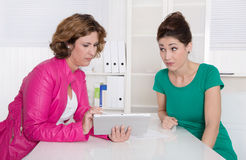 两名女实业家与片剂个人计算机一起使用在办公室。 库存照片