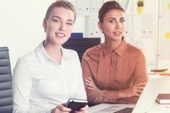 两名女实业家在一个白色办公室 免版税库存图片