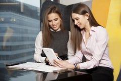 两名女实业家在办公室与膝上型计算机一起使用 库存图片