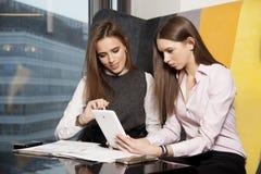 两名女实业家在办公室与膝上型计算机一起使用 免版税库存照片