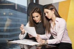 两名女实业家在办公室与膝上型计算机一起使用 免版税图库摄影