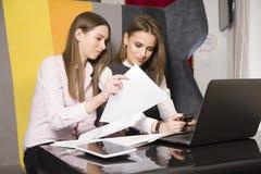 两名女实业家在办公室与膝上型计算机一起使用 图库摄影