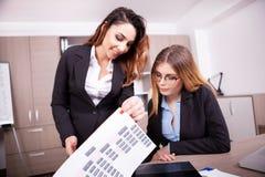 两名女实业家在看throug图的办公室 图库摄影