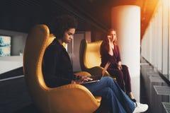 两名女实业家坐扶手椅子临近办公室窗口 库存图片