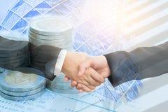 两名女实业家握手和硬币两次曝光在银行 免版税图库摄影