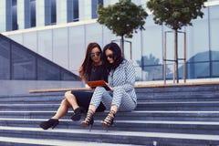 两名女实业家画象在时髦的正式衣裳穿戴了,看通过某事由片剂计算机 免版税图库摄影