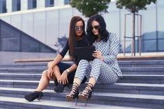 两名女实业家画象在时髦的正式衣裳穿戴了,看通过某事由片剂计算机 库存图片