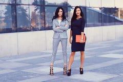 两名女实业家画象在穿戴了时髦的正式衣裳,站立在摆在反对背景的街市  库存图片