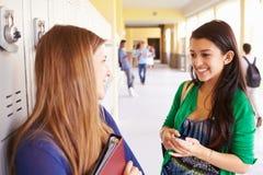 两名女性高中学生谈话由衣物柜 库存照片
