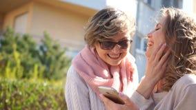 两名妇女一张快乐的画象有一个智能手机的在他们的手上 母亲和女儿笑的身分在中部 股票视频