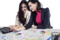 两名妇女与文书工作和膝上型计算机一起使用 库存图片