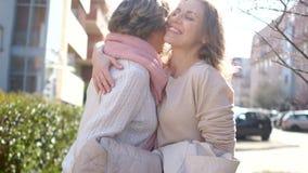两名妇女会议在城市街道上的在春天 老人和年轻女人拥抱并且继续前进 r 影视素材