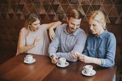 两名妇女和一个人咖啡馆的,谈,笑和享用thei 免版税库存照片