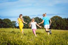两名妇女和女孩嬉戏在夏天草甸 图库摄影