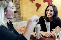 两名妇女喝和谈话在咖啡馆 免版税库存图片