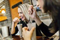 两名妇女喝和谈话在咖啡馆 免版税库存照片