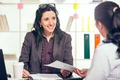 两名妇女在办公室互相聊天 免版税库存图片