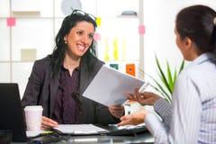 两名妇女在办公室互相聊天 库存图片