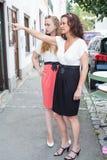 两名妇女在古雅街道上的窗口购物 免版税图库摄影