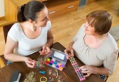 两名妇女在家做镯子 免版税库存照片