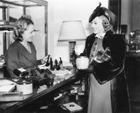 两名妇女在管子商店(所有人被描述不更长生存,并且庄园不存在 供应商保单那里将b 免版税图库摄影