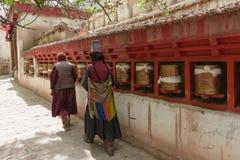 两名妇女在香客衣服转动的祈祷的轮子穿戴 免版税图库摄影