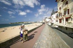 两名妇女在Fr步行沿着向下海滩木板走道在St吉恩在彻特巴斯克人的de Luz,南西部法国,一个典型的渔村 免版税库存照片