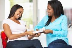 两名妇女坐交换礼物的沙发 库存照片