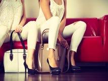 两名妇女坐提出袋子的沙发 库存图片