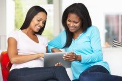 两名妇女坐有片剂计算机的沙发 免版税库存图片