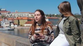 两名妇女坐桥梁街市的背景布拉格和谈话 通过回顾的船和的妇女 股票视频