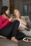 两名妇女坐观看电视饮用的酒的沙发 免版税库存照片