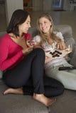 两名妇女坐观看电视饮用的酒的沙发 免版税库存图片