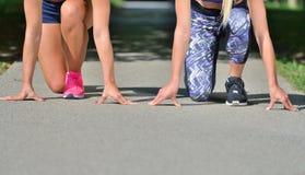 两名妇女实践的解决-健身室外在公园 库存图片