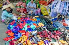 两名妇女审查五颜六色的凉鞋和鞋子待售在一个室外市场上在陈5月,越南 图库摄影