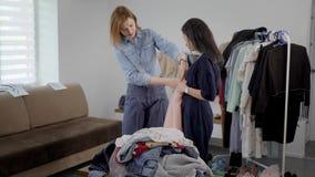 两名妇女接近制表与在舱内甲板的,采取裙子和播放对身体的衣裳堆 股票视频