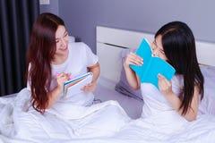 两名妇女文字和读书在床上的一本书在卧室 库存图片