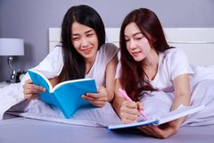 两名妇女文字和读书在床上的一本书在卧室 免版税库存照片