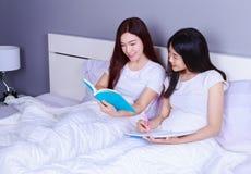 两名妇女文字和读书在床上的一本书在卧室 免版税图库摄影