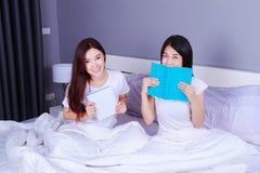 两名妇女文字和读书在床上的一本书在卧室 库存照片