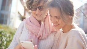 两名妇女春假、画象有一个电话的在他们的以春天太阳为背景的手上和开花的树 影视素材