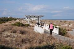 两名妇女横跨在沙丘的一座桥梁漫步到一个木拱道到车行道 库存图片