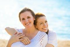 两名妇女母亲和享受在海滩的成人女儿假期 免版税库存照片