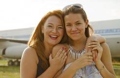 两名妇女母亲和女儿在机场见面了在旅行以后 免版税库存图片