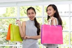 两名妇女满意对购物袋在手边 购物夫人smilin 免版税图库摄影
