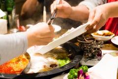 两名妇女烹调中国shabu hotpot 免版税库存图片