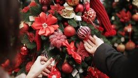 两名妇女特写镜头看红色圣诞装饰垂悬在购物中心的圣诞树 股票录像